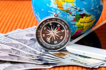 Five Hundred American Dollars Bank Notes, Compass, Globe of Planet Earth, tablet on a Fabric Background Closeup. Travel, tourism, Discovery Concept.