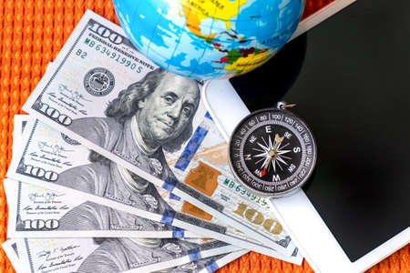 Five Hundred American Dollars Bills, Compass, Globe of Planet Earth, tablet on a Fabric Background Closeup. Travel, tourism, adventures Concept.