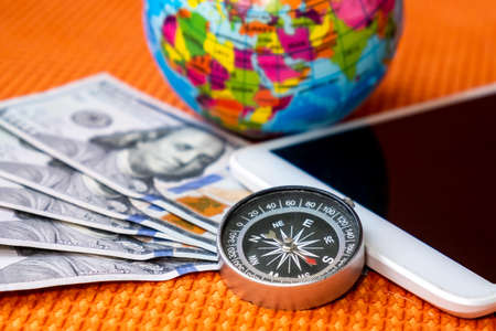 Five Hundred American Dollars, Compass, Globe of Planet Earth, tablet on a Fabric Background Close-up. Travel, tourism, adventures Concept.
