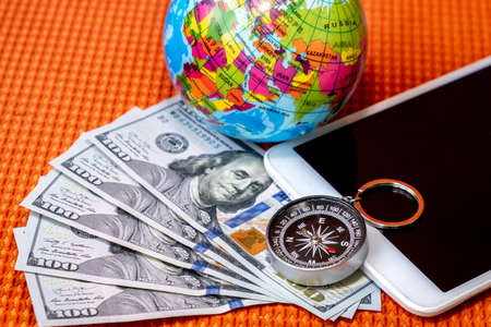 Five Hundred Dollars USA, Compass, Globe of Planet Earth, tablet on a Fabric Background Texture Close-up. Travel, tourism, adventure Concept.