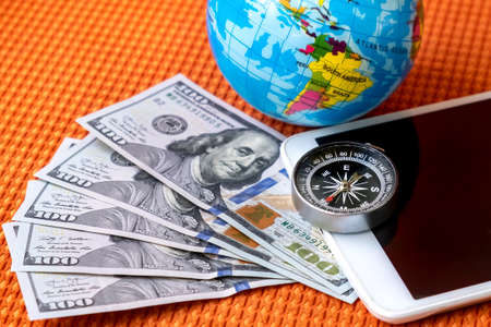 Five Hundred Dollars USA Banknotes, Compass, Globe of Planet Earth, tablet on a Fabric Background Closeup. Travel, tourism, adventure Concept.