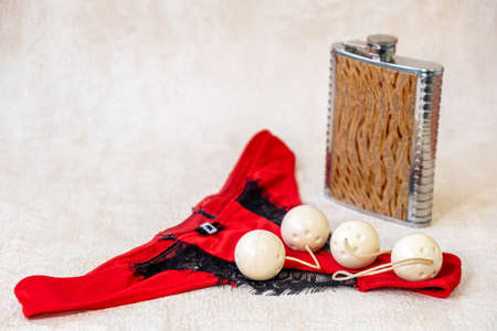 Female red bikini panties, metal flask with an alcohol drink and sex toy of four vaginal balls for sensual satisfaction.