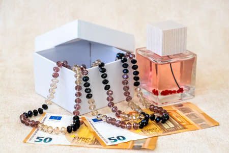 Beautiful Female Beads in White Gift Box, Perfume,  and Paper Banknotes Euro Lay on a White Textured Background. Stock Photo