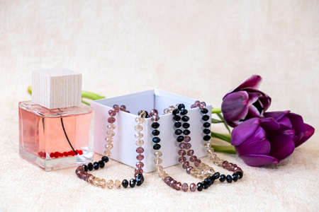 Burgundy color tulips flowers, female beads in a white gift box and Eau de Toilette.  Wonderful gift for a woman.