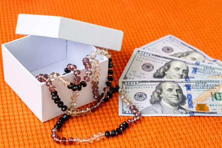 Beautiful Female Beads in White Gift Box and US Paper currency Dollars Lay on a Orange Fabric Textured Background. Stock Photo