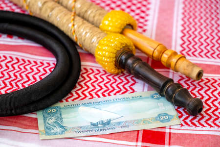 Arab Money Dirham Bank note, , hookah and Traditional Arab Male Clothes - kaffiyah and agal  close-up. Stock Photo