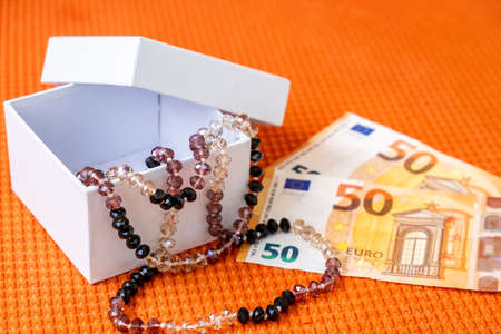 Beautiful Female Beads in White Gift Box and Paper Banknotes Euro Lay on a Orange Fabric Textured Background.