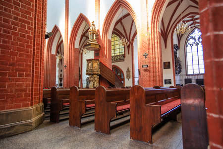 WROCLAW, POLAND - MAY, 2018. Row of Wooden Chairs in Interior of a medieval catholic cathedral, No People.