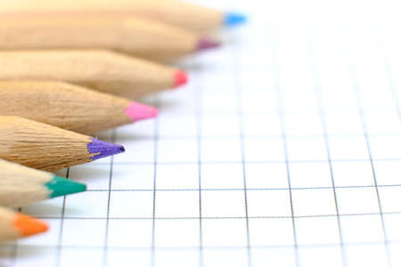 Closeup set of  colorful pencils on the checkered paper sheet of notebook for the drawing. Back to school concept. Copy space, no people. Shallow depth of field