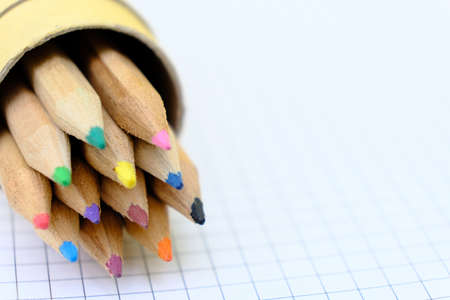 Closeup set of colorful pencils in a box on checkered paper sheet of notebook for the drawing. Back to school concept. Copy space, no people. Shallow depth of field