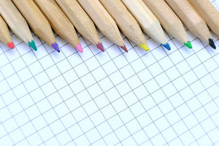 Closeup set of  multicolored pencils on the checkered paper sheet of notebook for the drawing. Back to school concept. Copy space, no people. Shallow depth of field