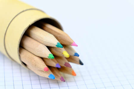 Closeup set of  multicolored pencils in a box on checkered paper sheet of notebook for the drawing. Back to school concept. Copy space, no people. Shallow depth of field 免版税图像