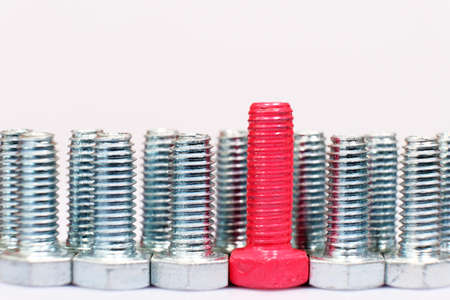 Close-up of red bolt in a group of galvanized metallic screws.
