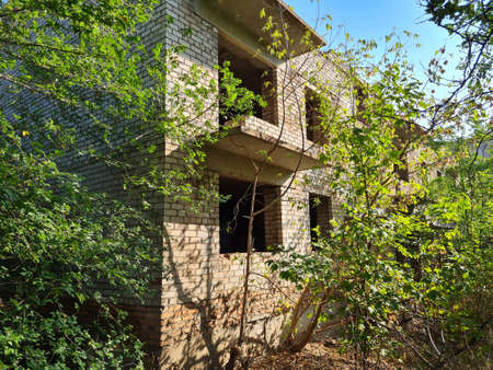 Unfinished abandoned brick apartment building overgrown with green trees at sunny summer day.