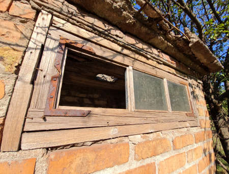 Background of old aged brick wall of abandoned bulding with window at sunny day. Wide angle.