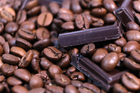 Close-up of dark roasted coffee beans and chocolate background. Aromatic coffee grains and sweet choco pieces macro photography, depth of field.