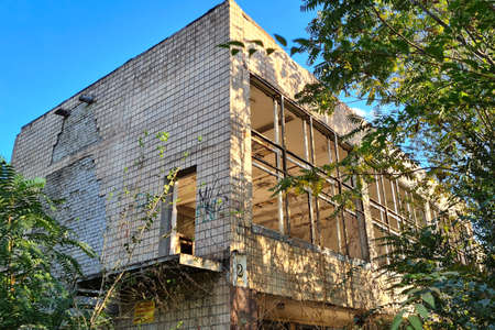 Unfinished abandoned munitipal building overgrown with green trees at sunny summer day.