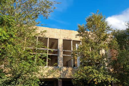 Unfinished abandoned office building overgrown with green trees at sunny summer day.