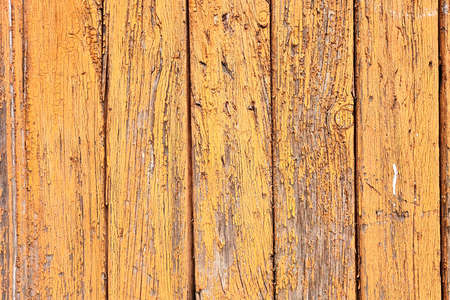 Texture of an old wooden wall of abandoned building with peeled yellow paint abstract background.