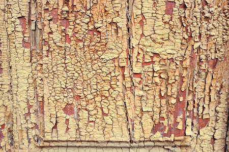 Texture of an old wooden door of abandoned building with peeled yellow paint abstract background.
