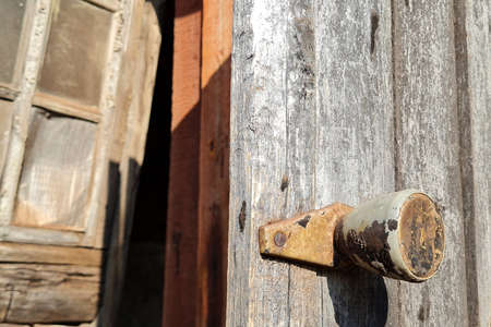 Rusty iron handle on old wooden door of abandoned village house. Abstract grunge, vintage background.