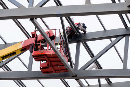 Man worker on a crane performs high-rise work on welding metal structures of a new tower at a height. 写真素材