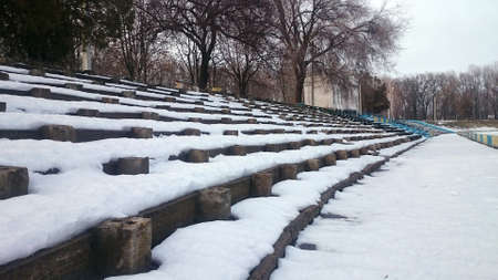 Snow-covered concrete stands of an old abandoned small stadium on a cloudy winter day.