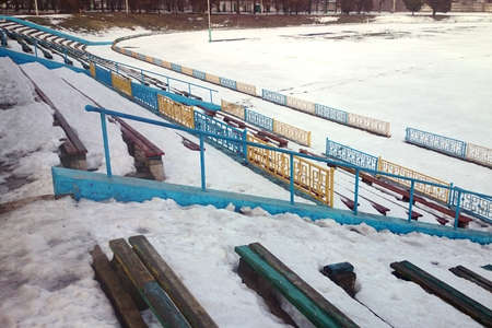 Snow-covered wooden stands of an old abandoned small stadium on a cloudy winter day.