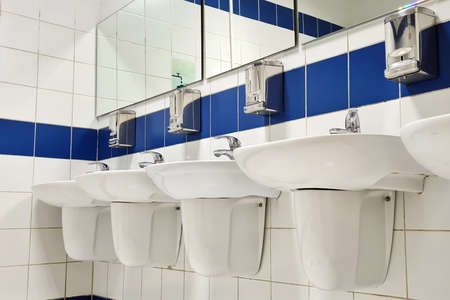 Group of white porcelain wash basins in public restroom at shopping mall.