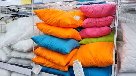 Many beautiful colorful pillows sells on a shelf in the store.