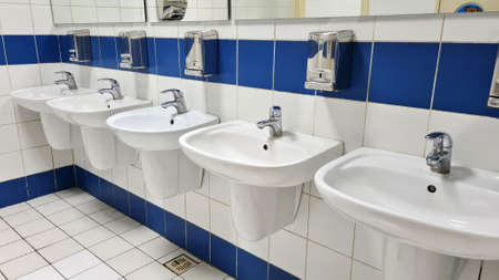 5 white porcelain wash basins in public restroom at shopping mall. 写真素材