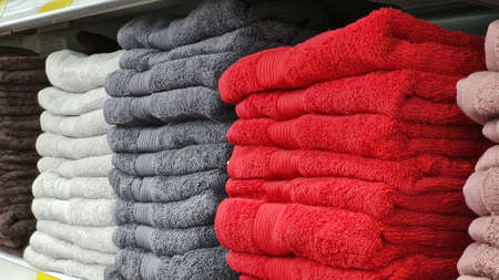 Stacks of beautiful white, gray, red towels sells on a showcase in the store. Scandinavian style, lagom. Archivio Fotografico