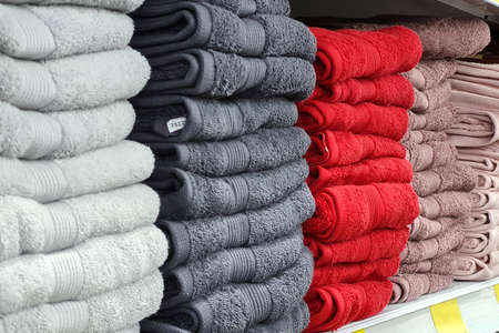 Stacks of beautiful white, gray, red towels of pastel colors sells on a showcase in the store. Scandinavian style, lagom. Archivio Fotografico