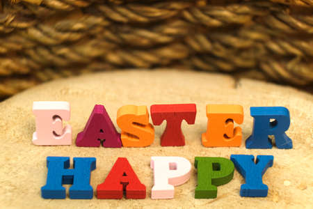 Words Happy Easter of colorful toy alphabet letters on on wooden table and wicker basket background. Ideal for design of bright greeting card with copy space. Shallow depth of field. Stock Photo