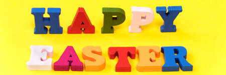 Text Happy Easter of colorful toy alphabet letters isolated on yellow background. Ideal for design of bright festive web banner.