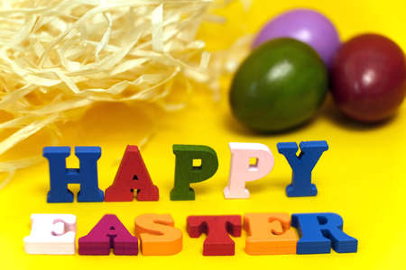 Text Happy Easter of colorful toy alphabet letters and painted multi colored eggs isolated on yellow background. Ideal for design of bright greeting card with copy space. Shallow depth of field. Stock Photo