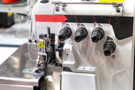 Close-up of details of modern white professional electric sewing machine on a table in factory. Work place of seamstress. No People.