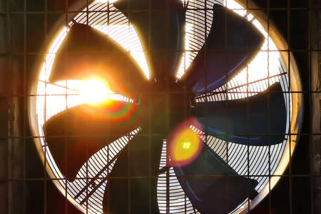 Close-up of big industrial fan in a factory. Ventilation of plant building. Backlit, sun light, rays of light.