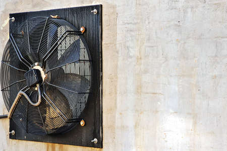 Big industrial fan in a white brick wall of a factory. Ventilation of factory building outdoors. Background with copy space Stock Photo