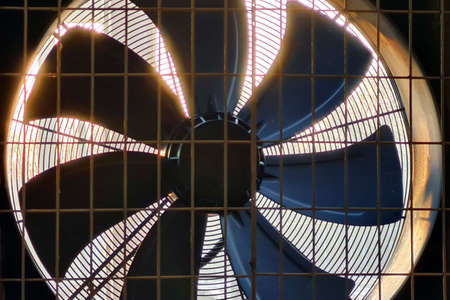 Close-up of big industrial fan in a factory. Ventilation of plant building. Back light.
