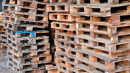 Many Old Used Wooden pallets is stack outdoors in the warehouse of cargo delivery enterprise. Stock Photo