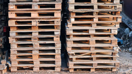 Many Old Used Wooden pallets is stack outdoors in the store of logistic enterprise.