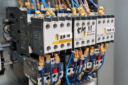 Close-up of magnet starters in a row in electrical cabinet of automation control industrial system. Stock Photo