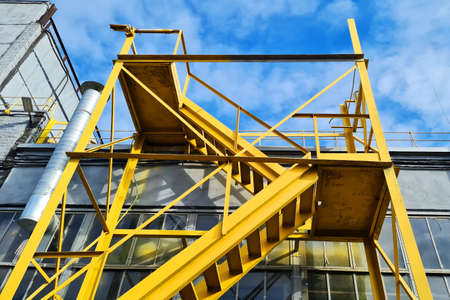 Big Yellow Staircase Near Industrial Plant Building on a Blue Sky Background At Sunny Bright Day. Bottom perspective view.