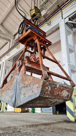 Rusty grab bucket or clamshell hanging on overhead crane in empty industrial plant. Stock Photo