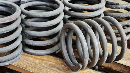 Many steel springs of shock absorbers on a wooden palete. Spare parts of heavy industrial machinery.