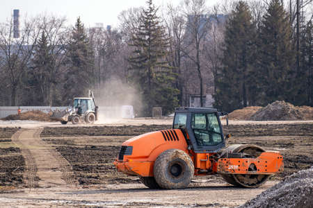 Soil skating rink works to seal ground the base of road. Construction Heavy Industrial Machines Build a New Highway. Stock Photo