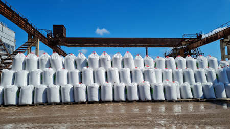 Many white big bags with chemical fertilizers in a warehouse outdoors. Stack of sacks in a 3 row on a blue sky background at sunny day.
