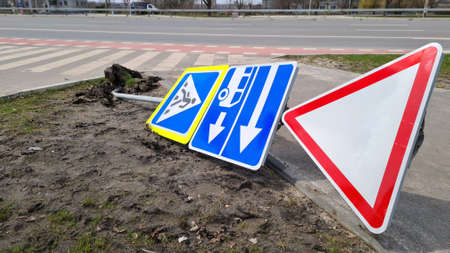 Damaged Broken Traffic Signs With Bus Direction Arrow and Pedestrian Crossing Road are Laying on the ground on Urban Street.