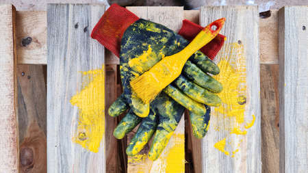 Black work protective gloves and a paintbrush smeared with yellow paint lie on a wooden pallet.